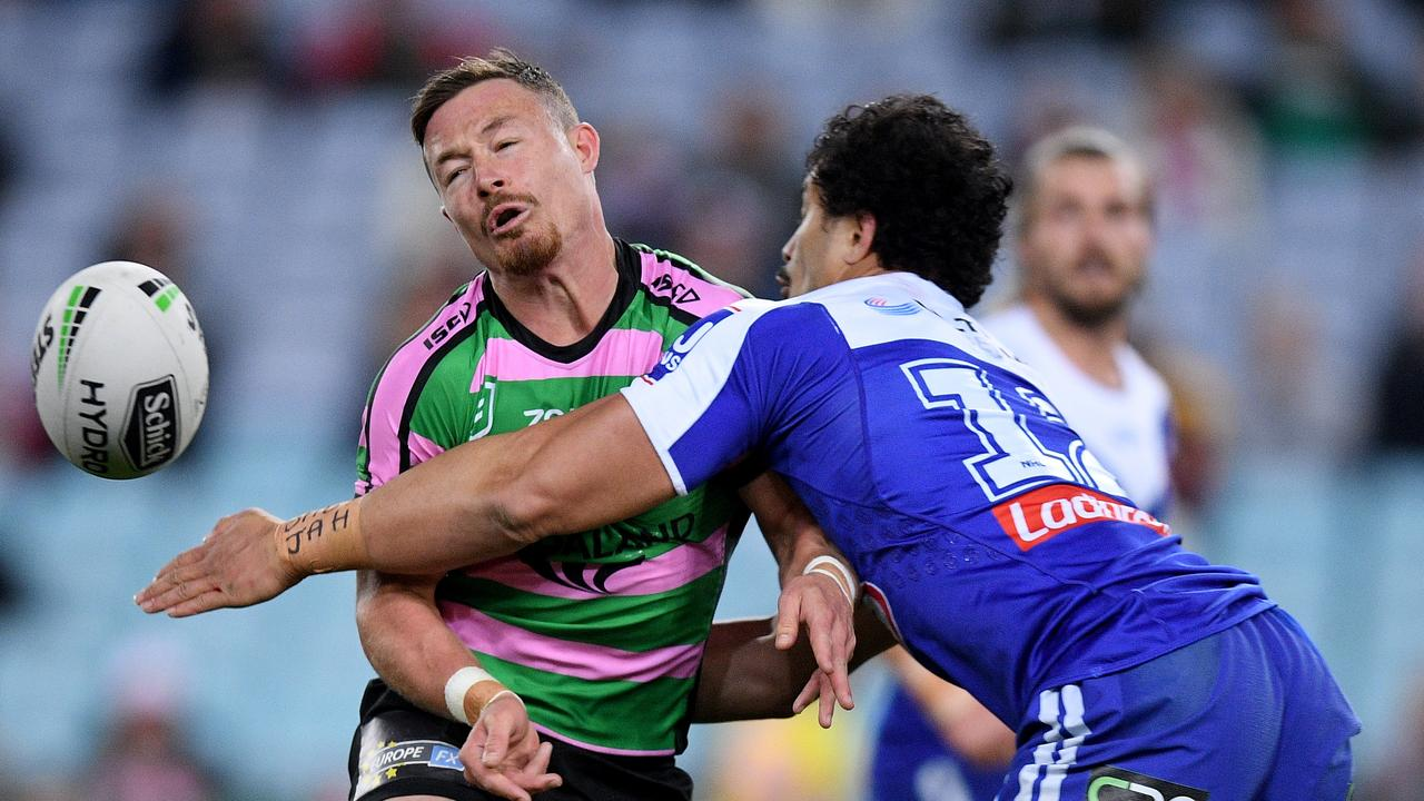 Damien Cook of the Rabbitohs is tackled by Corey Harawira-Naera