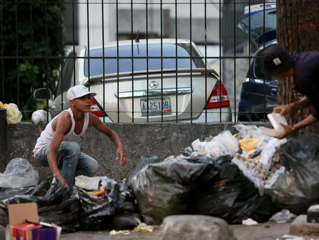 People look for food in the garbage due the extreme food shortages at Sabana Grande on January 31, 2019 in Caracas, Venezuela. Picture: Edilzon Gamez/Getty Images