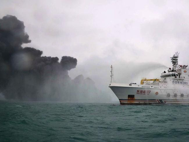 """The Chinese firefighting vessel """"DONGHAIJIU 117"""" spraying water on the burning oil tanker Sanchi at sea off the coast of eastern China."""