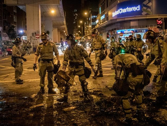 Police clean debris from the road after pro-democracy protesters set fire to a barricade during a protest gathering in front of Mong Kok police station. Picture: Getty
