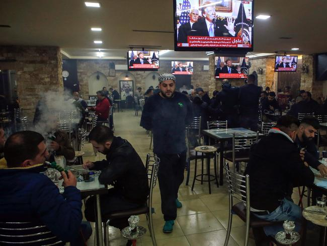 Palestinians sit in a cafe in the West Bank city of Ramallah watch Donald trump's speech. Picture: AFP/Abbas Momani