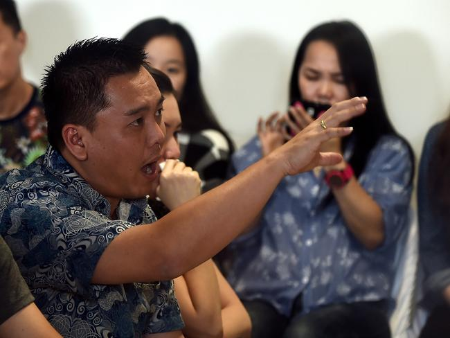 A family member of passengers on-board missing Malaysian air carrier AirAsia flight QZ8501 reacts angrily during a briefing inside the crisis-centre set up at Juanda International Airport in Surabaya. Picture: AFP/ Manan Vatsyayana
