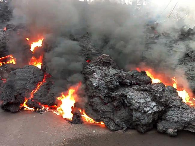 In this photo from video a lava flow advancing down a road is seen from the Leilani Estates subdivision near Pahoa on the island of Hawaii. Picture: AP