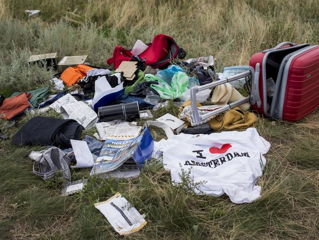 Luggage and personal belongings from Malaysia Airlines flight MH17 lie in a field, all 298 on board including 80 children died in the crash. Picture: Rob Stothard/Getty Images