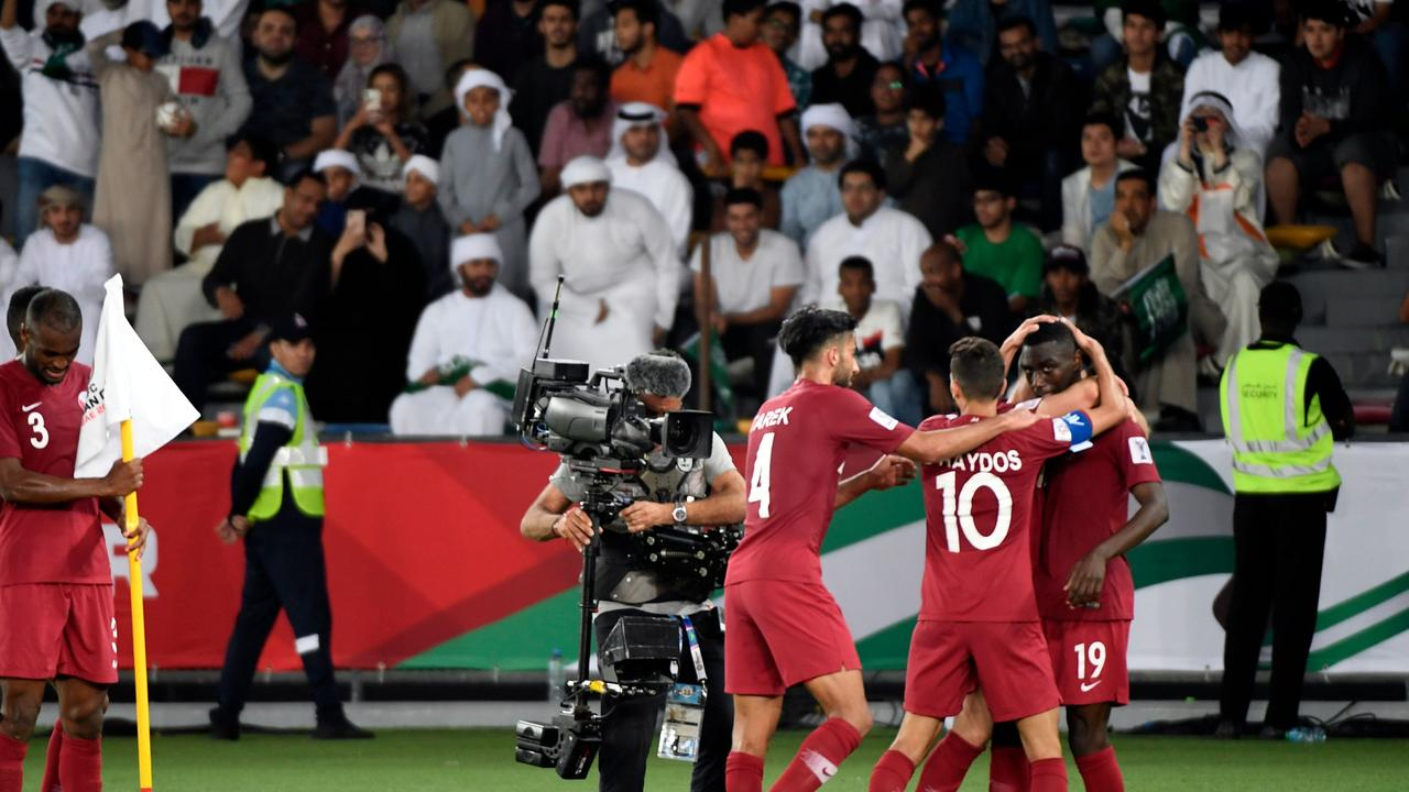 Qatar's forward Almoez Ali (R) is congratulated by teammates after scoring