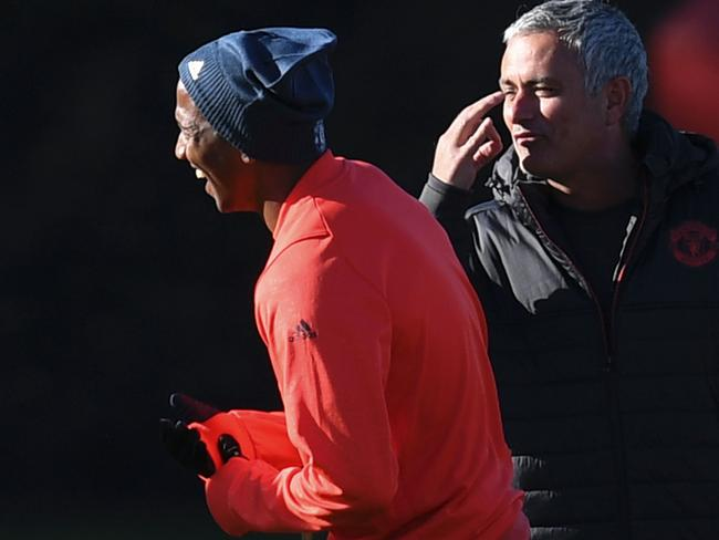 Manchester United's Portuguese manager Jose Mourinho (R) jokes with Ashley Young.