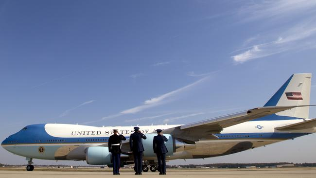 Military personnel salute as Air Force One, with President Barack Obama aboard departs Andrews Air Force Base.