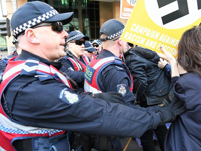 Victorian Police officers push back protestors outside the Magistrates court in Melbourne on Monday. Picture: AAP Image/James Ross