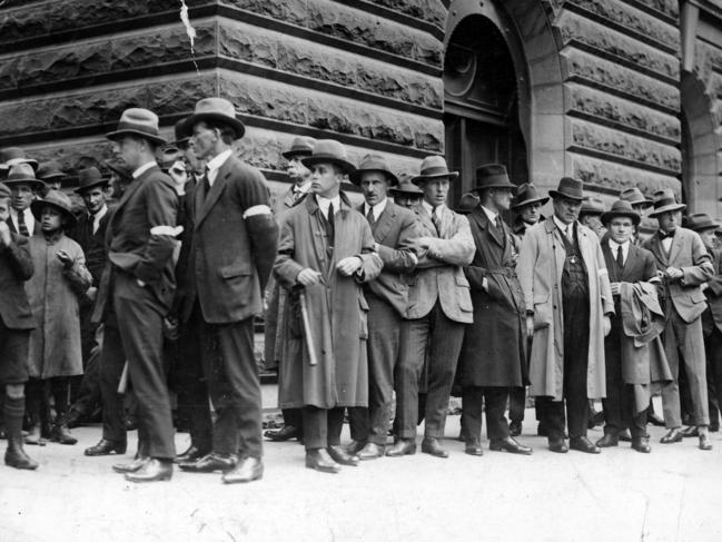 Newly enlisted special constables, some wearing official armbands, some with batons, queue outside the Town Hall.