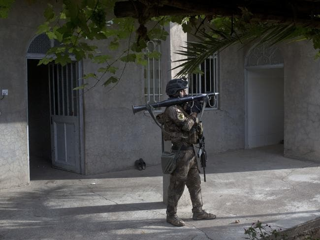 An Iraqi special forces soldier holds a rocket-propelled grenade launcher as his unit searches a house in Gogjali. Picture: Marko Drobnjakovic.