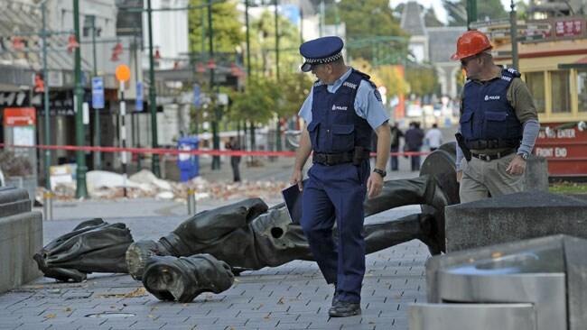 Two police officers walk past a fallen statue in Christchurch / AP