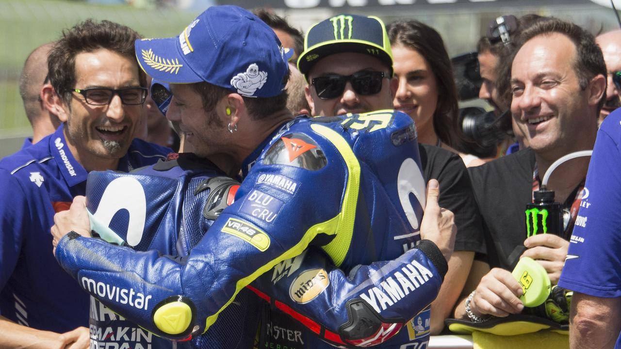 Valentino Rossi is embraced after taking pole in Italy.