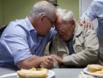 Prime Minister Scott Morrison comforts 85-year-old Owen Whalan of Half Chain Rd in Koorainghat who was evacuated from his home during a visit to Club Taree Evacuation Centre on Sunday. Picture: AAP/Darren Pateman