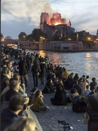 Mourners gathered on the banks of the Seine River as flames destroyed the roof of the building.
