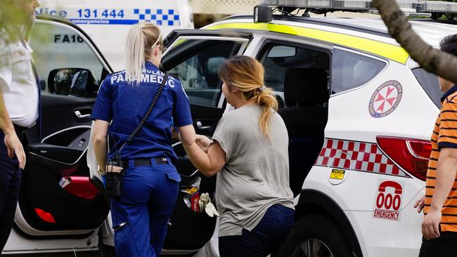 Police and paramedics speak with a family member. Picture: Jenny Evans