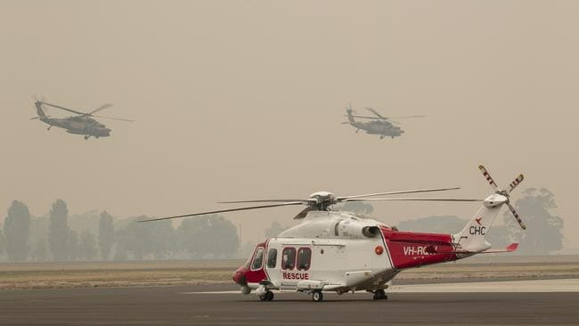Two Australian Army Blackhawk helicopters fly through the smoke haze at the RAAF Base in Victoria on January 3. Picture: AAP Image/Supplied by the Department of Defence, Nicole Dorrett
