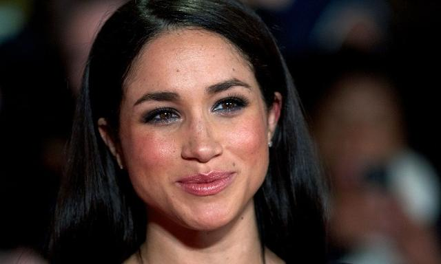 """(FILES) This file photo taken on November 11, 2013 shows US actress Meghan Markle poses for pictures on the red carpet upon arrival for the world premier of the film """"The Hunger Games: Catching Fire"""" in Leicester Square, central London, on November 11, 2013. Britain's Prince Harry will marry his US actress girlfriend Meghan Markle early next year in 2018 after the couple became engaged earlier this month, Clarence House announced on November 27, 2017. / AFP PHOTO / Andrew Cowie"""