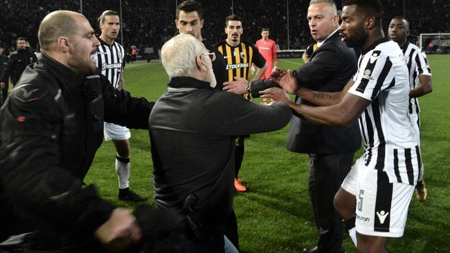 Paok president Ivan Savvidis (C) takes to the pitch carrying a handgun