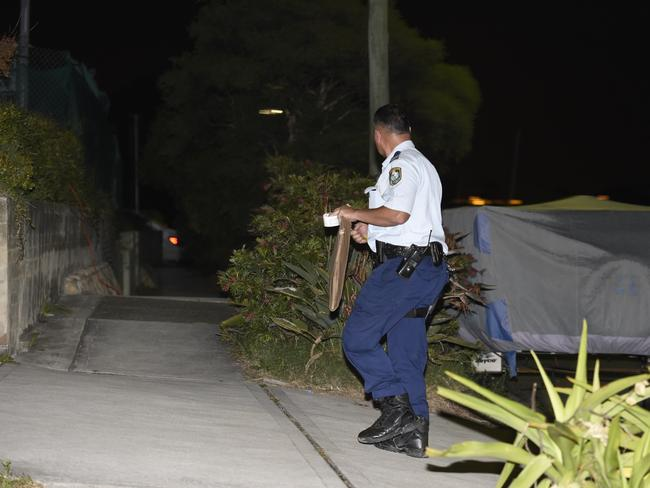 A police officer looks for evidence at the scene. Picture: Gordon McComiskie