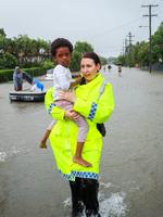 Senior Constable Natasha Dibben carries 3 yr old Gabby Uwase out of flood waters in Hermit Park assisting residents to safely get out. Flooding in Townsville today. Photo: Michael Chambers. 02/02/2019