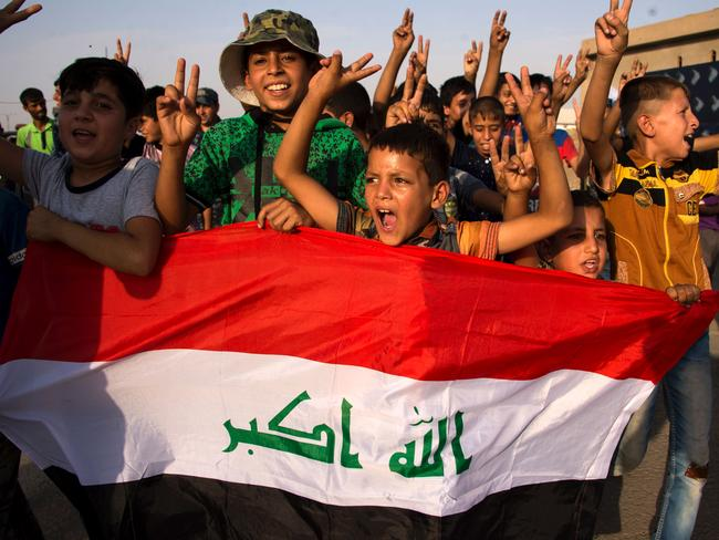 """Children holding Iraq's national flag react as Iraqi forces celebrate in the Old City of Mosul on July 9, 2017 after the government's announcement of the """"liberation"""" of the embattled city. Picture: Fadel Senna"""