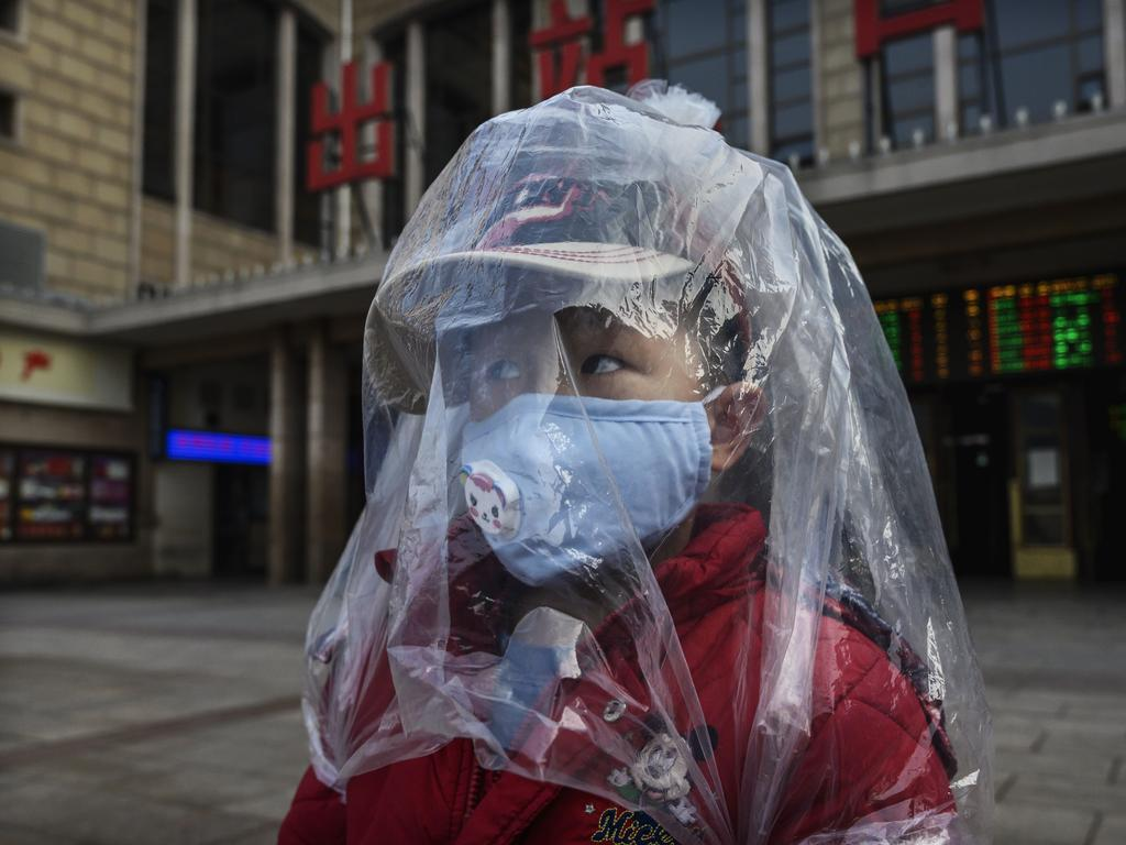 A Chinese boy covered in a plastic bag for protection in Beijing. Picture: Kevin Frayer/Getty Images
