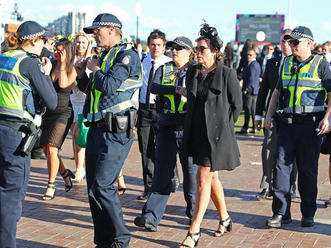 A female racegoer is taken away by police officers. Picture: Scott Barbour