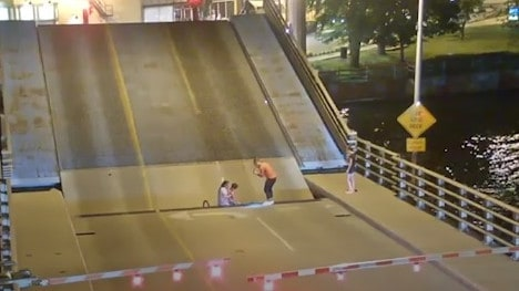 Pedestrians rush to her aid and retrieve her from the gap. Source: Storyful