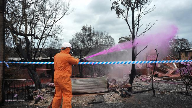 Hazmat crews are seen spraying asbestos bonding agent in the NSW coastal town of Tathra, after homes were destroyed by fire, causing the release of the harmful building product into the atmosphere. Picture: Perry Duffin/AAP