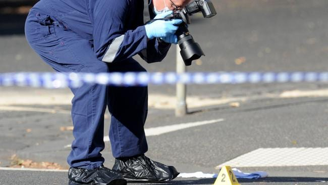 Police collect evidence at the scene on King Street, West Melbourne. Picture: Andrew Henshaw