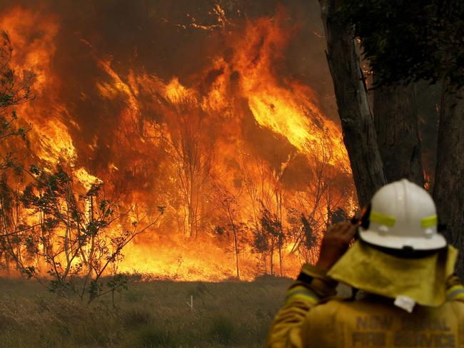 A firefighter on property protection watches the progress of bushfires in Old Bar, NSW, Saturday, November 9, 2019. Two people have been killed and seven others are missing in bushfires in NSW which have also destroyed at least 100 homes. (AAP Image/Darren Pateman)