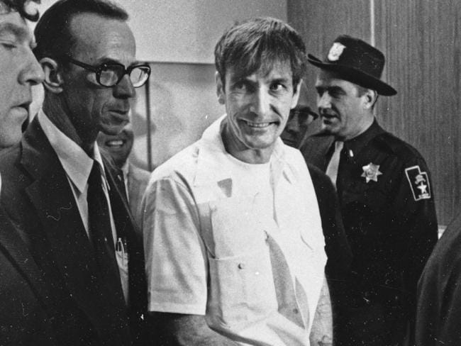 Gary Gilmore arrives heavily guarded to a court appearance in Utah in 1976.