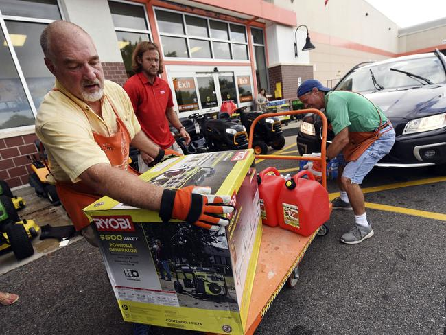 Jim Craig, David Burke and Chris Rayner load generators as people buy supplies at The Home Depot in Wilmington, N.C. Picture: Ken Blevins/The Star-News via AP