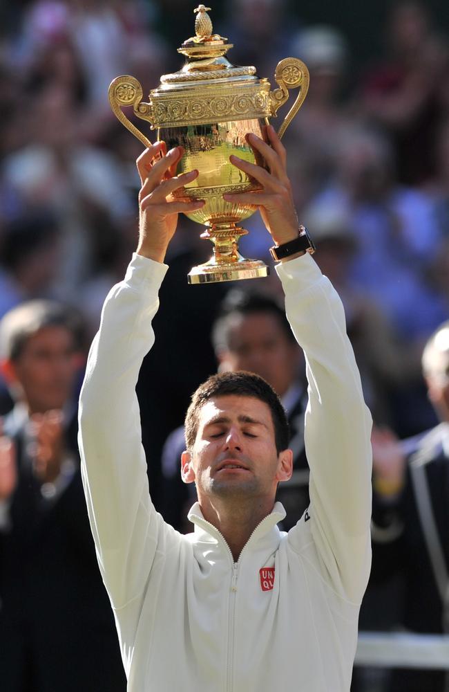 Novak Djokovic raises the Wimbledon trophy.