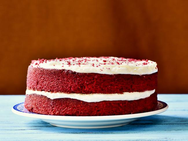 an appetising red velvet cake on a rustic blue wooden table