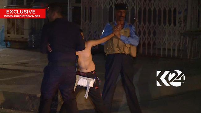 In this still taken from local TV footage, a child is shown being restrained by security forces, holding his arms out-stretched as another man cuts off a belt of explosives.