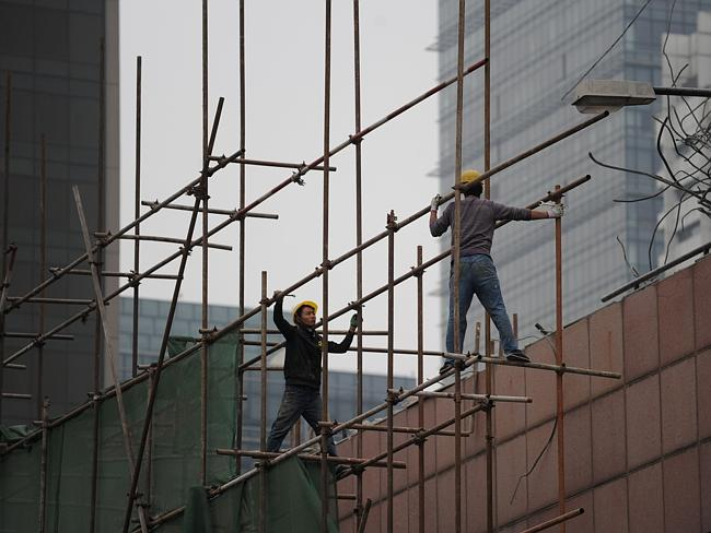 A slowdown in China's economy has implications for Australia's mining sector. Pictured, Chinese workers in Beijing.