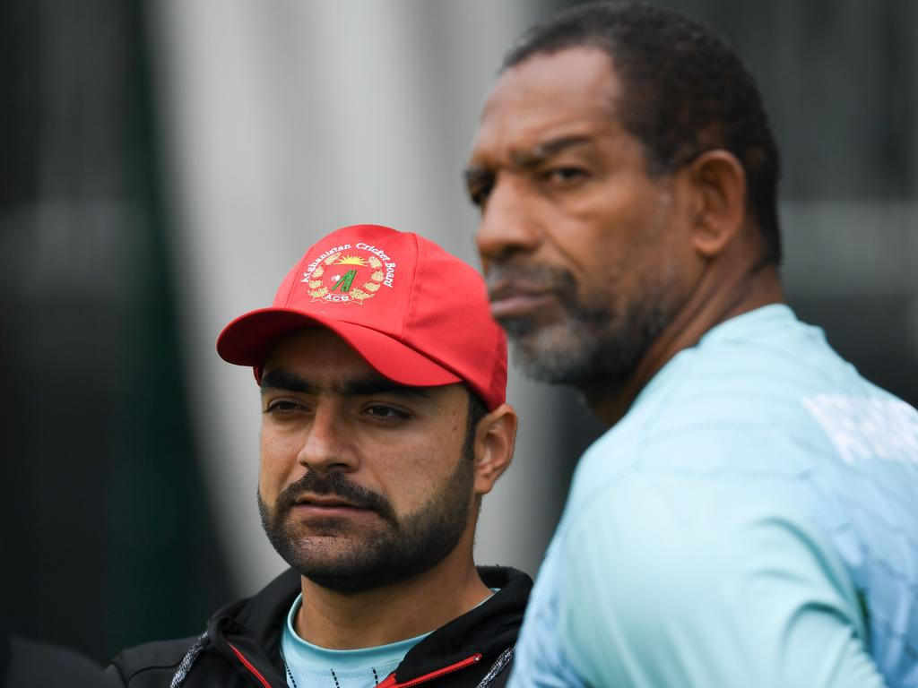 Afghanistan's Rashid Khan (L) and Afghanistan's head coach Phil Simmons (R) attend a training session at Old Trafford Cricket Ground in Manchester, northwest England, on June 17, 2019, ahead of their 2019 World Cup match against England. (Photo by Dibyangshu SARKAR / AFP)