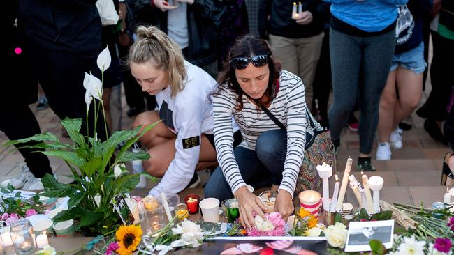 People place candles and flowers next to a photo of murdered British backpacker Grace Millane during the vigil for murdered British backpacker Grace Millane at Civic Square Park in Wellington. Picture: Marty Melville / AFP