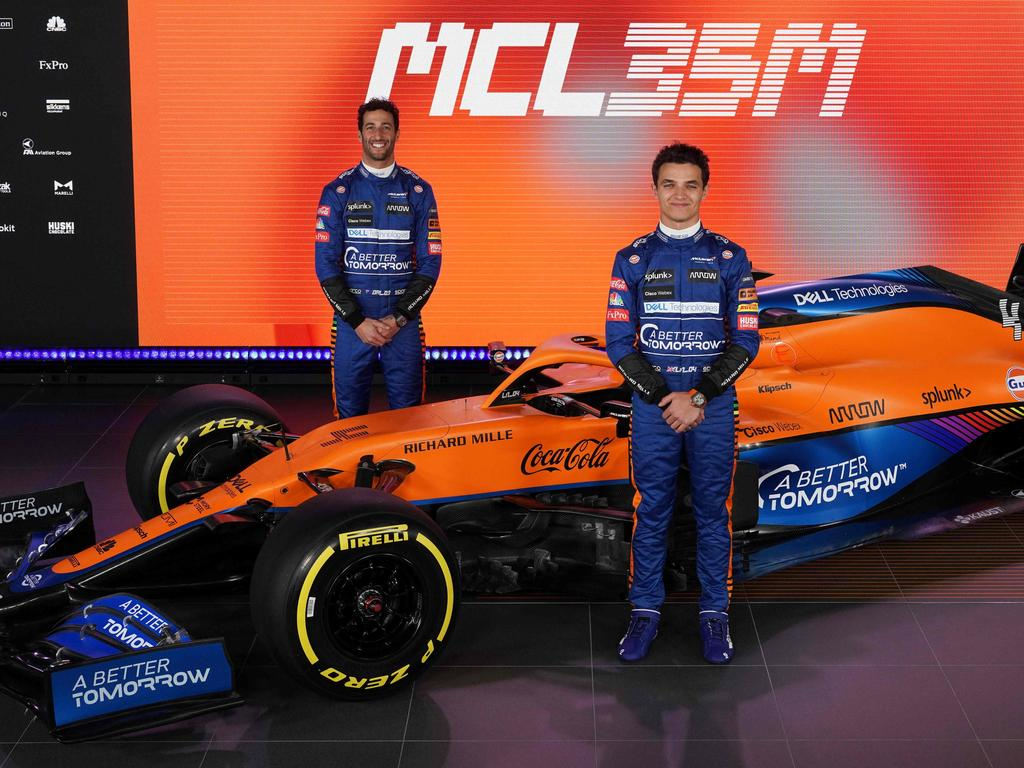 A handout photo released on February 15, 2021 by McLaren shows McLaren's British driver Lando Norris (R) and Australian driver Daniel Ricciardo posing by the new McLaren Formula 1 car MCL35M in Woking, southwest of London. (Photo by Handout / McLAREN / AFP)