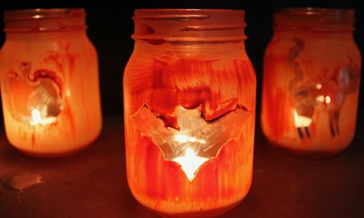 <b>MASON JAR LANTERNS.</b> All you really need are a few mason jars and some orange paint but the effect of these spooky mason jars is great for creeping the kids out late at night.