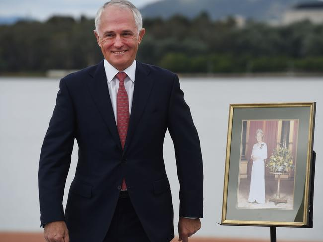 PM Malcolm Turnbull stands with a portrait of Queen Elizabeth II at an Australia Day citizenship ceremony in Canberra, as debate rages about our nation becoming a Republic. Picture: AAP Image/Mick Tsikas