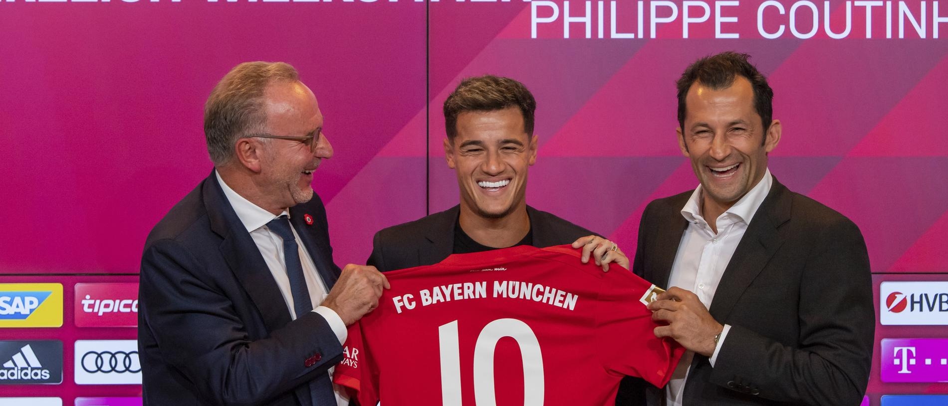 New player for Bayern Munich Philippe Coutinho, center, holds up a team shirt with his name on it with Karl-Heinz Rummenigge, left,  and coach Hasan Salihamidzic during a presser in their stadium in Munich, Germany, Monday, Aug. 19, 2019. Coutinho comes as a loaner for one year from FC Barcelona. (Peter Kneffel/dpa via AP)