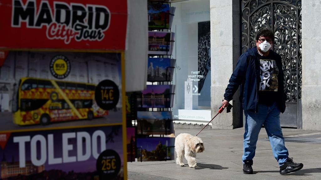 A man wearing a mask carries his dog in after regional authorities have ordered that all stores in the region be closed for fourteen days except those selling food, pharmacies and gas stations, in order to slow down the spread of coronavirus. Image: AFP