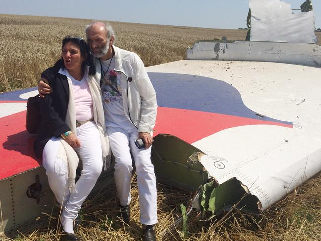 """We have promised our daughter we will come here."" ... Jerzy Dyczynski and Angela Rudhart-Dyczynski whose daughter, 25-year-old Fatima, was a passenger on Malaysia Airlines flight MH17, sit on part of the wreckage of the crashed aircraft in Hrabove, Ukraine. AP Photo/Nicholas Garriga"