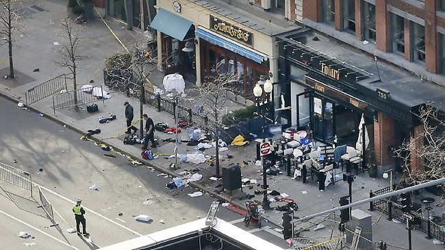One of the blast sites on Boylston Street near the finish line of the 2013 Boston Marathon is investigated and guarded by police in the wake of two blasts in Boston.