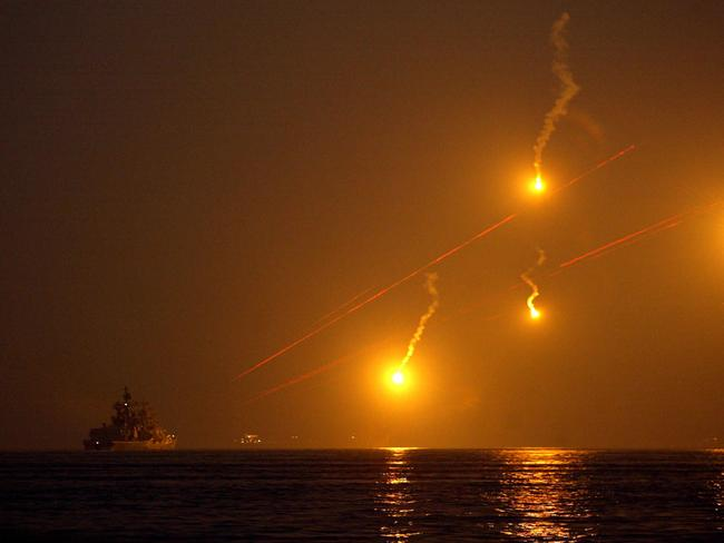 Flares burst in the sky as Chinese warships practice night antimissile and anti-aircraft drills.