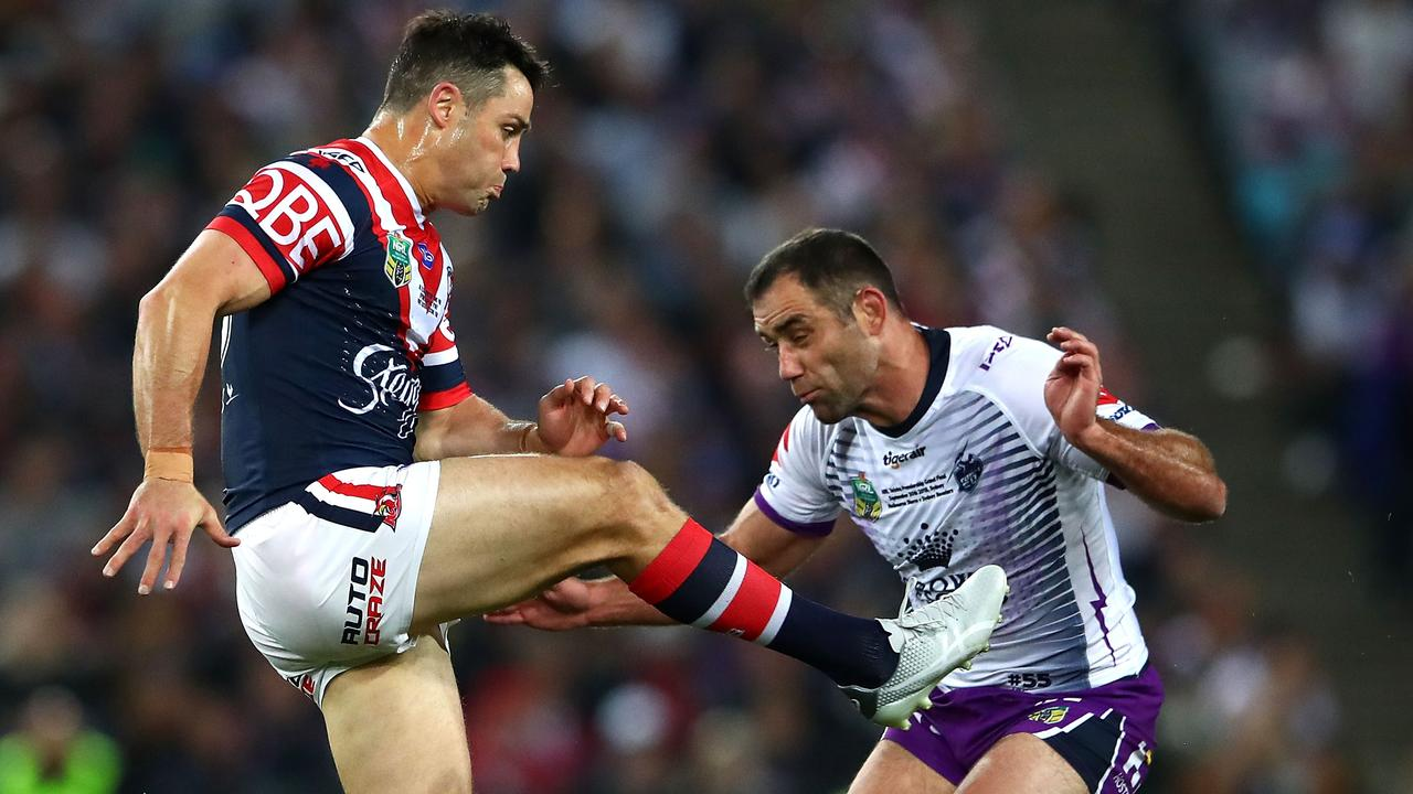 Cameron Smith of the Storm tackles Cooper Cronk of the Roosters after kicking the ball.