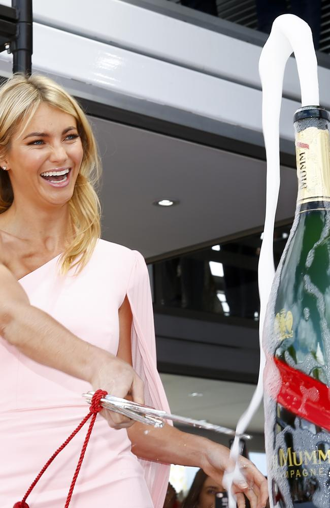 Mega-sleeve didn't stop her from knocking the top off a giant bottle of champers.