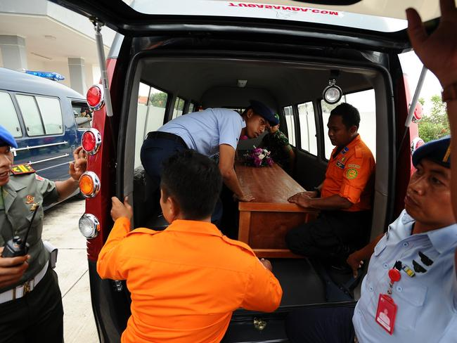 Indonesian soldiers place a coffin containing a victim into a vehicle at Indonesian Military Base Airport. Picture: Robertus Pudyanto